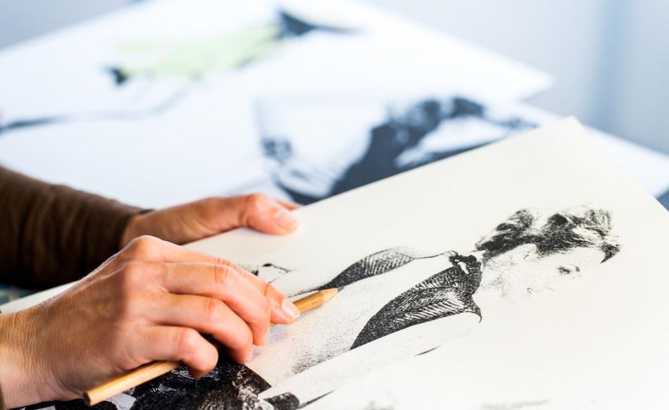 37426907 - extreme close up of female fashion designers hand creating fashion sketch.